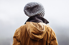 The back of a guy wearing a heavy coat and beanie