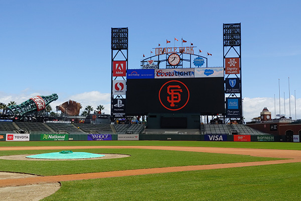 Baseball field with jumbotron displaying the SF Giants Logo