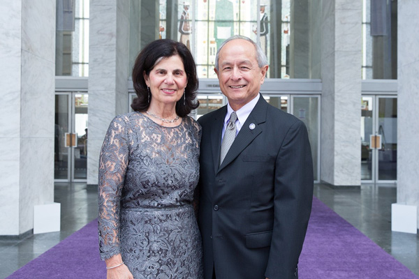 Mr. and Mrs. Wong standing on purple carpet in front of a marble and glass building