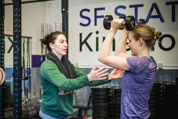 Female fitness instructor helping another woman exercise with dumbbells