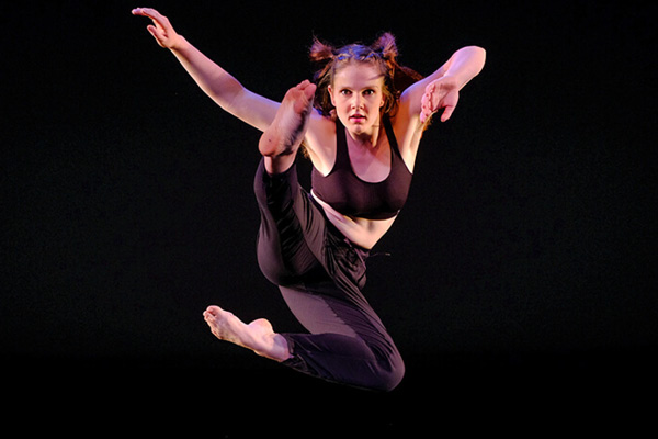 Woman in the air with arms spread out and one leg kicked