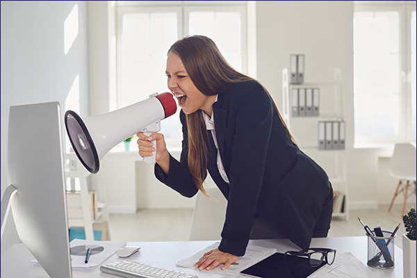 woman screaming at a computer with a bullhorn